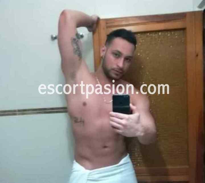 hombre escort de cuerpo musculoso se hace una selfi en el baño