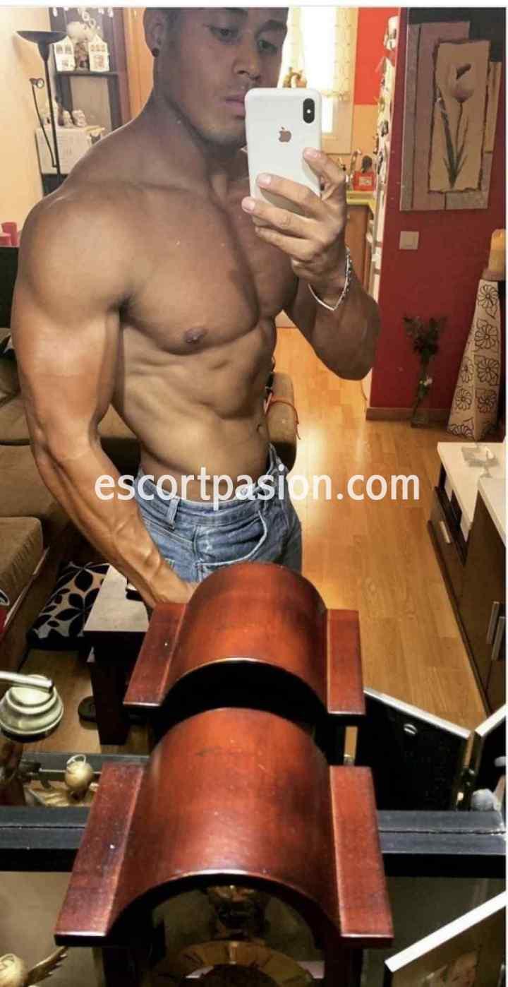 hombre escort se hace una selfi mostrando sus musculos