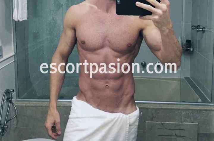 gigolo de cuerpo atlético se hace una selfi, es un hombre muy caliente en la cama