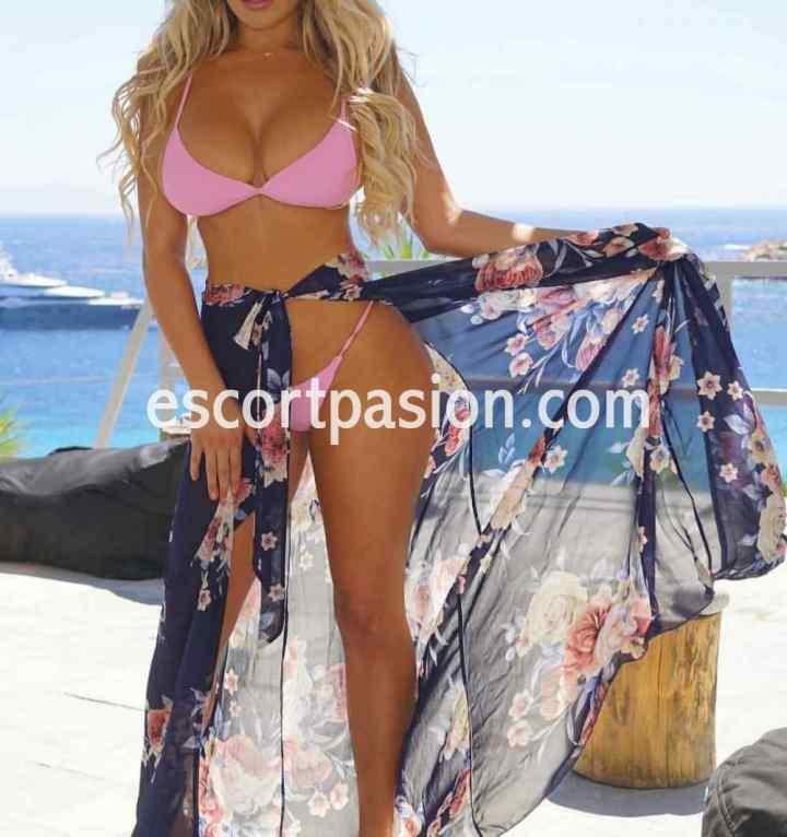 escort rubia de caderas prominentes en bikini tomando sol en la playa