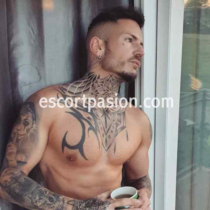 masajista hombre con el cuerpo tatuado miranod por la ventana
