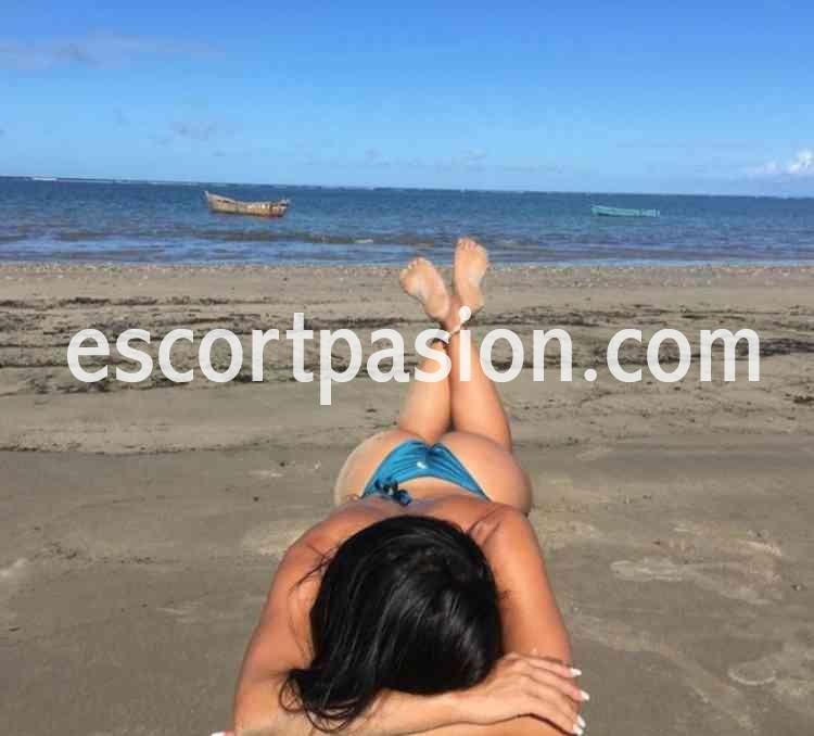 escort morena en bikini tomando el sol en la playa