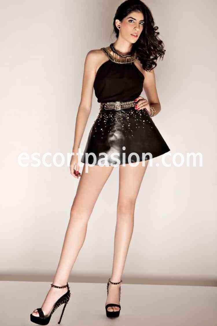 escort elegante con vestido negro y tacones hace francés natural
